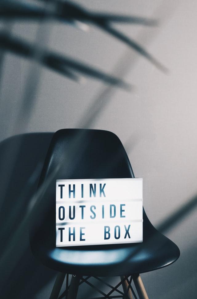 """Ein schwarzer Stuhl mit einem Schild darauf, auf dem Schild steht """"Think outside the box"""". Auf Deutsch """"Denken Sie über den Tellerrand hinaus"""""""