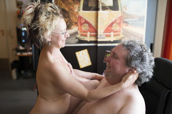 Eine Frau steht nackt vor dem Rollstuhl ihres Lebensgefährten, sie hält seinen Kopf in ihren händen, er greift nach ihrer linken Brust. Beide lächeln.
