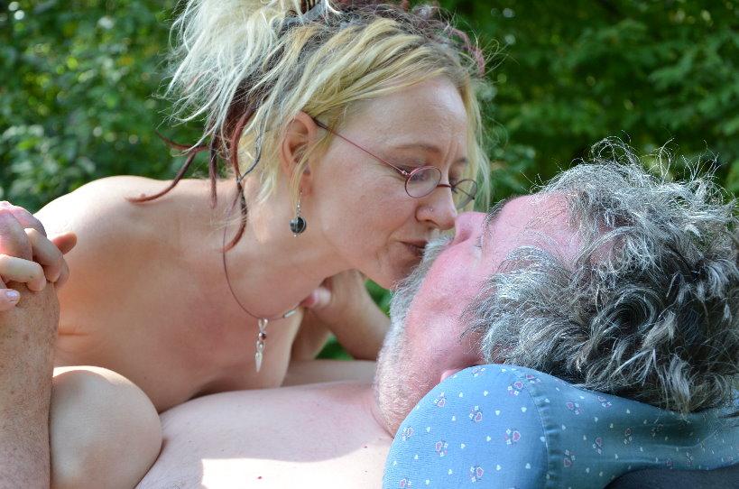 Eine Frau lehnt sich auf die Brust ihres Lebensgefährten, er sitzt in einem Elektrorollstuhl. Die beiden halten Händchen und berühren sich innig, Beide sind nackt.