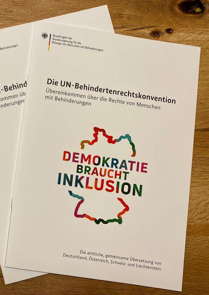 """Die gedruckte Version der UN-Behindertenrechtskonvention. Sie liegt auf einem Holztisch und trägt die Aufschrift """"Demokratie braucht Inklusion""""."""