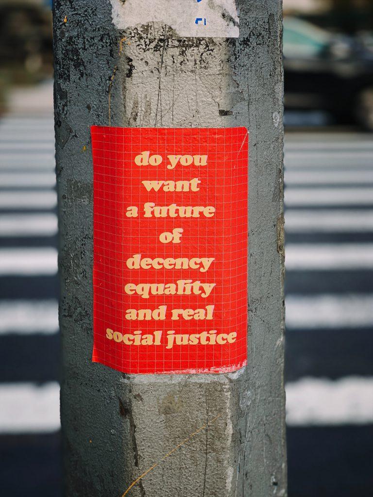 """Ein Holzmast aud dem ein roter Flyer klebt, darauf steht """"do you want a future of decency, equality and real social justice"""". Auf Deutsch """"Wollen Sie eine Zukunft voller Anstand, Gleichheit und echter sozialer Gerechtigkeit"""""""