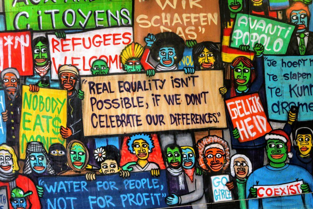 """Eine Zeichnung auf der bunte Menschen verschiedene Schilder hoch halten. Im Zentrum steht ein Schild mit der Aufschrift """" Real equalitiy isn`t possible, if we dont celebrate our differences"""", auf Deutsch """"Echte Gleichheit ist nicht möglich, wenn wir unsere Unterschiede nicht feiern""""."""