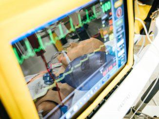 Ein Überwachungsgerät auf einer Intensivstation, im Spiegelbild sehen wir eine beatmete Puppe.