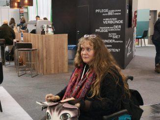 Wir sehen Patricia Koller, wie sie in ihrem blauen Rollstuhl sitzt und eine Handtache auf dem Schoß hat, die ein Katzengesicht zeigt. Im Hintergrund befindet sich ein Messestand des Bayerischen Ministeriums für Gesundheit und Pflege.