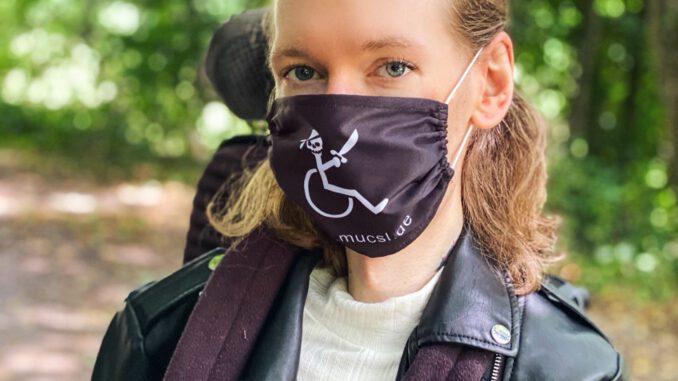 Christian Kiermeier steht auf einem Waldpfad, er trägt die MUCSL-Maske mit der Webadresse MUCSL.de und dem MUCSL-Logo darauf. Das Logo zeigt einen säbelschwingenden Piraten im Rollstuhl auf schwarzem Hintergrund.