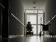 einsamer Korridor mit Gehhilfe und Elektro-Rollstuhl vor einer Glastür, in einem Pflegeheim.