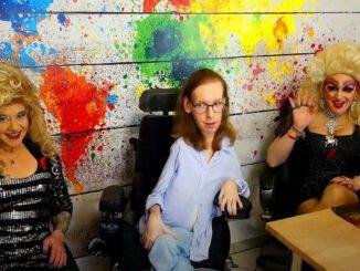 Die Drag Darlings und Ich sitzen vor einer bunten Wand, deren Farbkleckse den Kontinenten nachempfunden sind. Gina und Zoey winken in die Kamera.