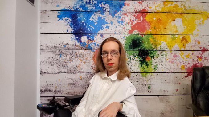 Ich sitze mal wieder vor meiner bunten Wand, mit den verschiedenfarbigen Kontinenten, um euch meine Neujahrsansprache 20/21 näherzubringen. Ich trage eine weiße Bluse und bin vergleichsweise unauffällig geschminkt, lediglich der rote Lippenstift ist etwas auffällig.