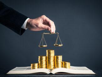 Ein Buch liegt aufgeschlagen da, darauf befinden sich verschiedene Stapel aus Goldmünzen. Eine männliche Hand hält eine kleine Waage über den Stapel. Ein Symbolbild für die ungleichen Löhne im Positionspapier zur Neugestaltung der Stundenlöhne für persönliche Assistenz im Arbeitgebermodell.